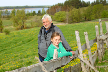 Grandfather with his granddaughter travel at attractive places.