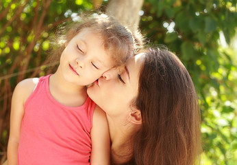 Happy young mother kissing her happy joying kid with love