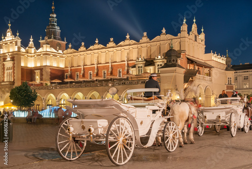 Carriages before the Sukiennice on The Main Market in Krakow - 68083296