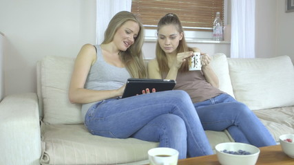 Two beautiful friends at home using a tablet talking and smiling