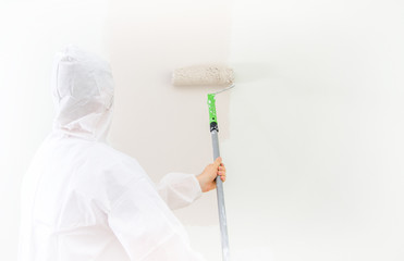 Painter in protective suit paints the wall.