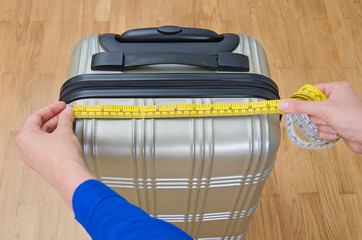 Hand luggage measurement using measuring tape.