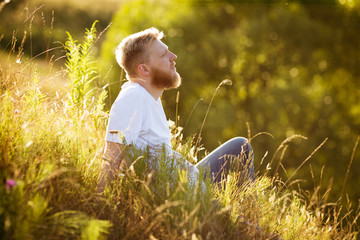 Happy man sitting on the grass and dreaming