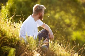 Happy man sitting on the grass