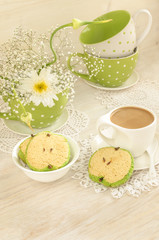 Bouquet of white flowers, cup coffee, apple shaped cookies