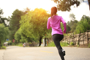 young woman runner athlete running on country road