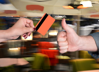 Woman holding credit card, man gesturing thumb up