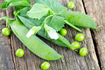 fresh pea pods on wooden surface