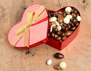 chocolate covered nuts and raisins in a heart-shaped gift box