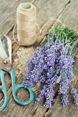 fresh lavender, scissors and thread on wooden surface