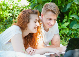 young couple and computer in the park