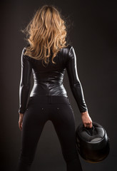 Sexy woman back and butts in black shiny dress and helmet