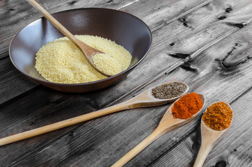 Spice on spoon with bowl of couscous