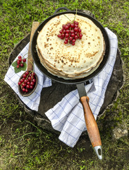 Pancakes with red currants on old pan and spoon