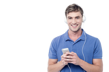 Young man enjoying music from his cell phone