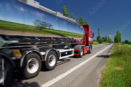 Mirroring the landscape chrome tank truck moving on a highway - 68090841