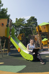 brunette using laptop on the playgrond