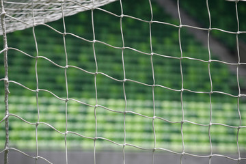White soccer net with green grass background
