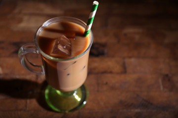 Glass of iced milk coffee on  wooden background