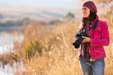 young female photographer holding camera outdoors