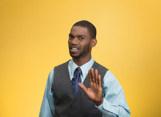 Angry executive gesturing with hands to stop, yellow background