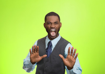 Angry executive gesturing with hands to stop, green background