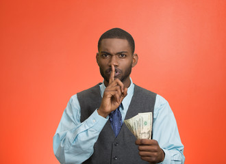 Bribery man with dollar bills in hand and quiet gesture