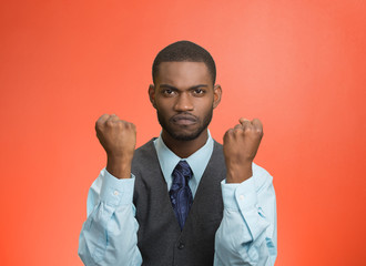 Angry man with fists up in air, isolated red wall  background