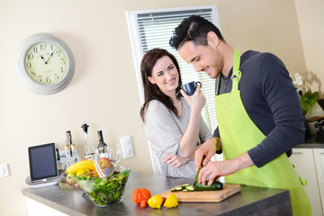 happy young couple preparing organic salad together in kitchen