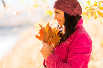 side view of young woman holding autumn leaves