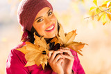 woman holding autumn leaves
