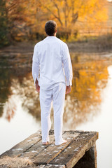 young man standing on lake pier