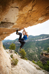 Female rock climber on overhanging cliff
