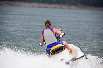 Young Woman piloting a personal water craft