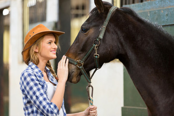 cowgirl and horse inside stable