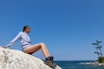 Young woman on big rock against blue sky