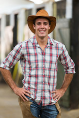 american cowboy standing in stables