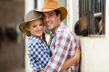 western couple hugging in stables
