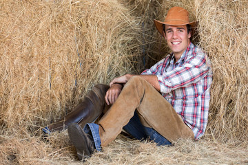 american western cowboy sitting on hay