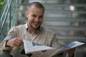 Handsome man reading newspaper