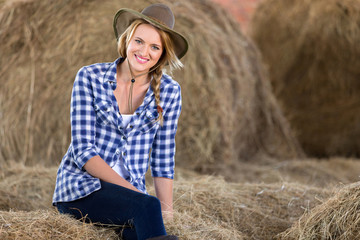cowgirl sitting on hay bales