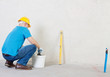 Plasterer man with trowel and bucket near plaster wall.