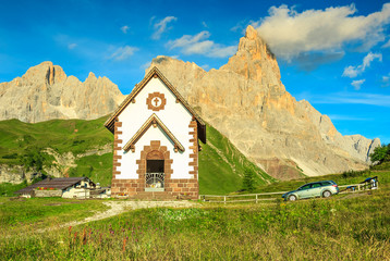 Tirolian chapel,car and high mountains,Dolomites,Italy,Europe
