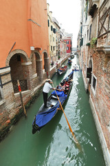 ourists floating in gondola in canal in Venice