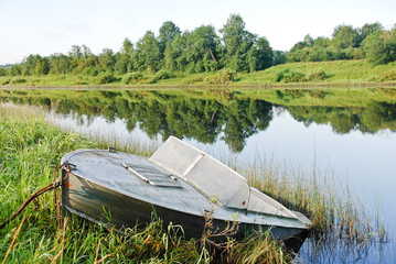 old boat on green shore of small river in summer