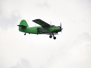 small green airplane flying in overcast sky