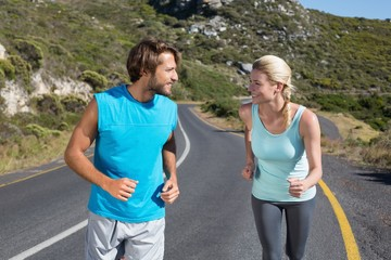Fit couple running together up a road