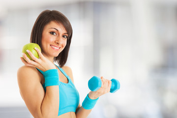 Woman holding an apple and a dumbbell
