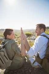 Hiking couple sitting on mountain terrain high fiving