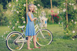 Summer Cycling - girl with dog in rose garden
